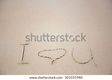 "words ""i love you"" written on sandy beach - stock photo"