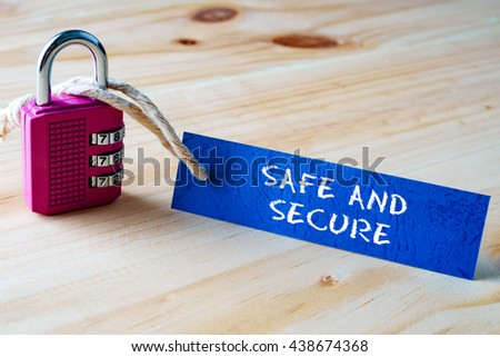 Words SAFE AND SECURE written on tag label tied with a padlock. - stock photo
