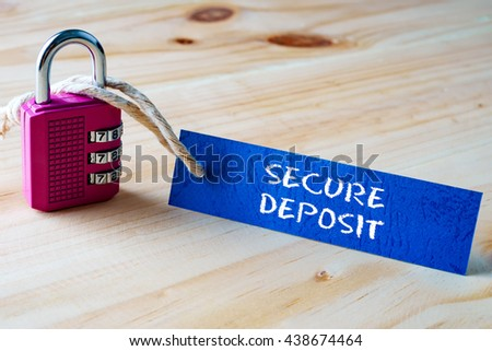 Words SECURE DEPOSIT written on tag label tied with a padlock. - stock photo