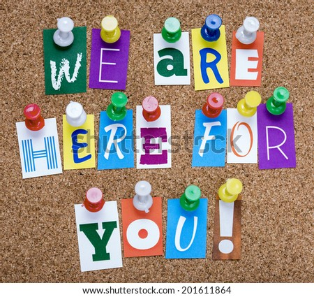 words we are here for you from cutout newspaper letters pinned to a cork bulletin board - stock photo