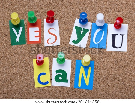 words yes you can from cutout newspaper letters pinned to a cork bulletin board - stock photo