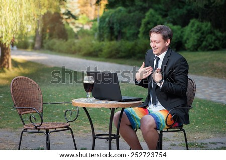 Work and relax. Online conference. Businessman dressed in suit and shorts working with laptop, talking by skype at the park cafe outdoors - stock photo