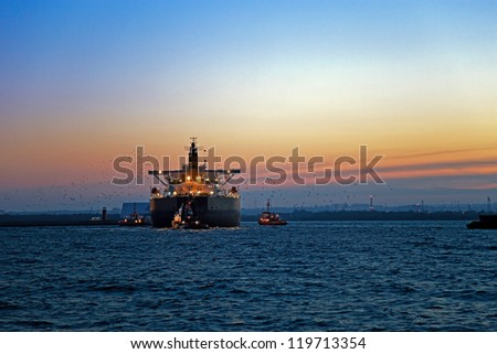 Work at sea after sunset - a cargo ship enters the port, escorted by tugboats. - stock photo