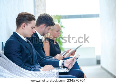 Work at the break. Confident businessman sitting in a waiting room and holding a laptop. Businesspeople sitting in a line and dressed in formal wear. - stock photo