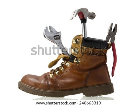 Work boot with hammer, pliers and wrench inside - stock photo