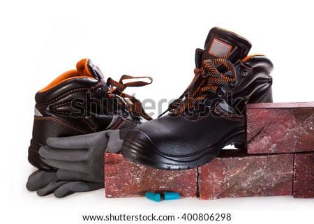 Work boots, decorative facing stone, gloves on a white background - stock photo