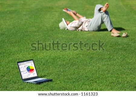 Work can wait! Laptop with Charts in the Grass and a Woman Lays in the Grass Reading - stock photo