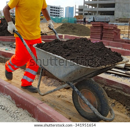 Work carries fertile soil in a wheelbarrow