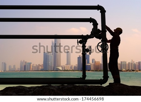 Work closes the valve on city background. - stock photo