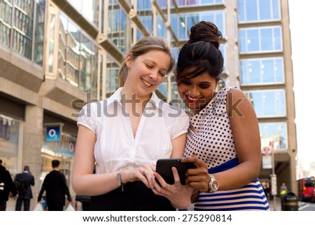 work colleagues looking at a computer in the street - stock photo