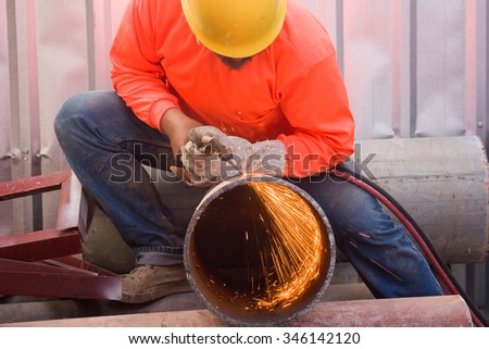 work cutting steel pipe using metal torch and install roadside fence - stock photo