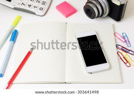 Work desk with blank notebook, smart phone, camera, calculator and pencil - stock photo