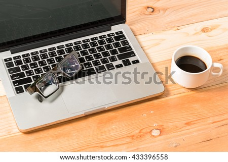 Work desk with laptop computer, eyeglasses and hot coffee cup. Top view rustic wooden table background with copy space