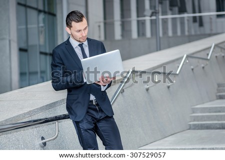 Work even at the break. Confident businessman coming down the stairs to the street and works at a laptop checking email from a client