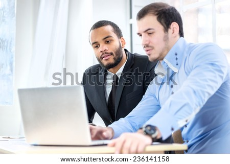 Work for the laptop. Two confident businessman with a smile check work in the laptop in the office of the table in the formal wear. - stock photo