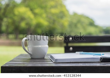 Work in the garden concept, Coffee cup with book on wooden table under the spring sunlight in a park. Using as background or wallpaper nature template