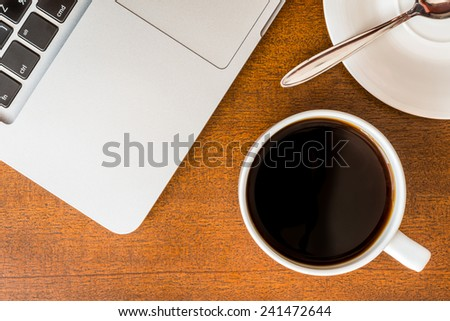 Work in the office, coffee cup and a plate with a spoon with laptop on the wooden table - stock photo