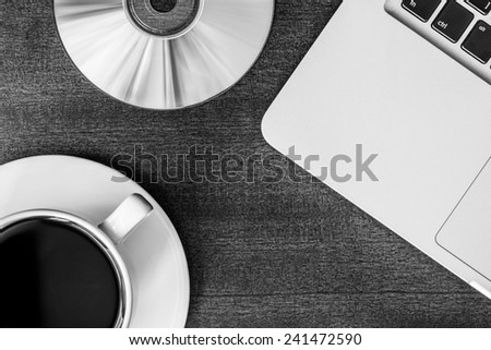 Work in the office, coffee cup and a plate with an optical disk with laptop on the wooden table - stock photo