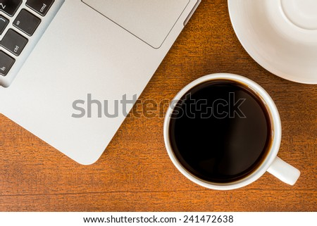 Work in the office, coffee cup and a plate with laptop on the wooden table - stock photo