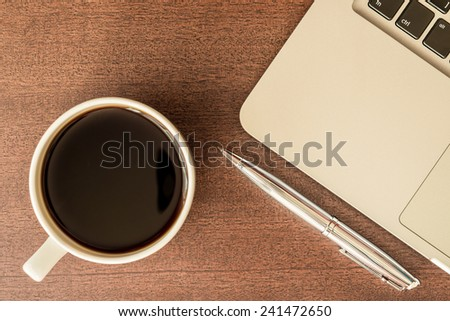 Work in the office, coffee cup with laptop and a pen on the wooden table. In yellow tone - stock photo
