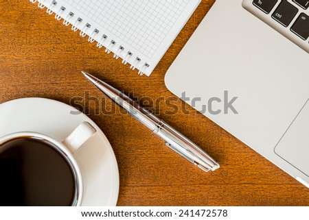 Work in the office, coffee cup with laptop and a pen with a notebook on the wooden table - stock photo