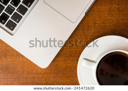 Work in the office, coffee cup with laptop on the wooden table - stock photo