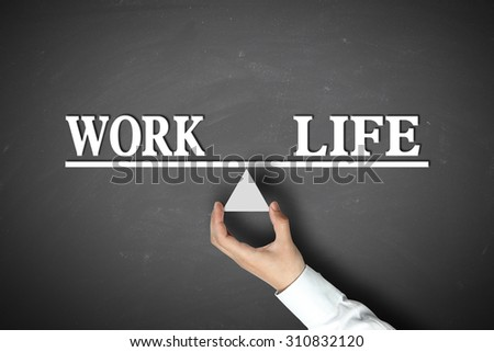 Work Life Balance concept with scale holden by businessman hand against the blackboard background. - stock photo