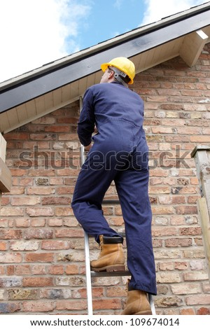 Work man climbing a ladder at the side of a house - stock photo