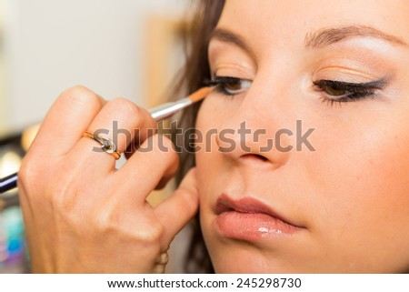 Work of make-up artist. Makeup artist apply makeup on the face of the girl model. Painting of eyebrows. Application of shadows on the model's eyes.