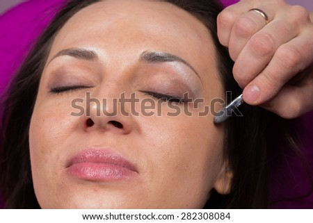 Work of make-up artist. Makeup artist apply makeup on the face of the girl model. Painting of eyebrows. Application of shadows on the model's eyes. - stock photo
