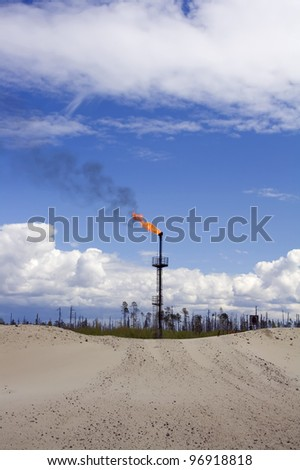 Work of oil and gas industry. Flame torch. Colorful blue sky with white clouds - stock photo