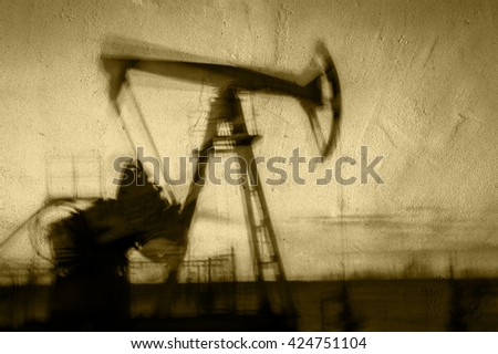Work of oil pump jack on a oil field. Textured concrete grunge, blurred motion.  Concept oil and gas industry. Toned sepia. - stock photo