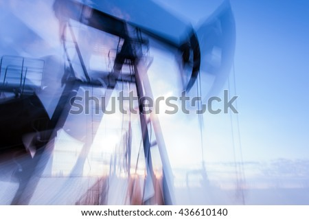Work of pump jack on a oilfield. Double long exposure, blurred motion.  Concept oil and gas industry.