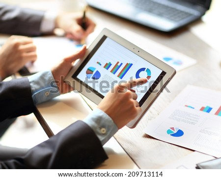 work of two young businessmen using touchpad at meeting - stock photo