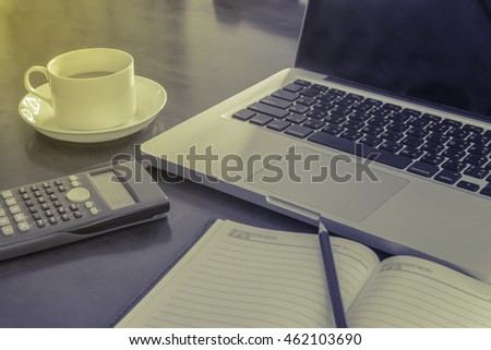 work on a wooden desk with a laptop and nootbook and calculator.vintage tone.selective focus