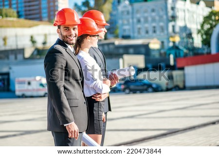 Work on the construction site. Three confident business architect in protective helmet standing in a row at the construction site while the African architect with a smile looking at the camera - stock photo