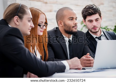 Work on the project. Confident businessman sitting at a laptop and edit business plan. Businessmen sitting at a table at a meeting in the office. - stock photo