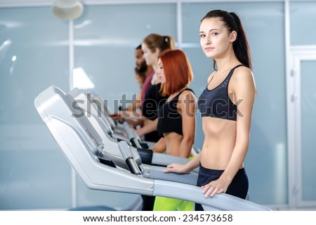 Work out in the gym. Sport and slender girl running on a treadmill and looking at the camera. Athlete dressed in sports uniforms and running in the gym. - stock photo