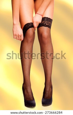 Work path isolated woman's hands reaching to pull up the mesh black stockings on her beautiful legs on high hills. - stock photo