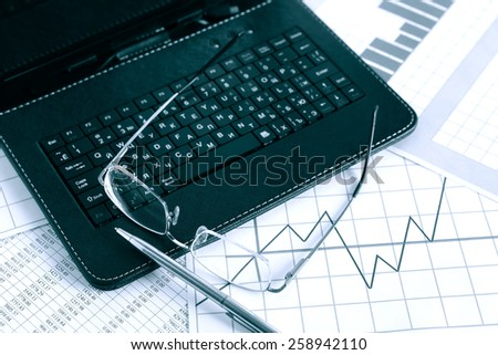 Work place. Closeup of spectacles near pen on laptop keyboard - stock photo
