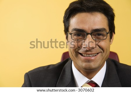 work place: successful businessman smiling and staring at the camera