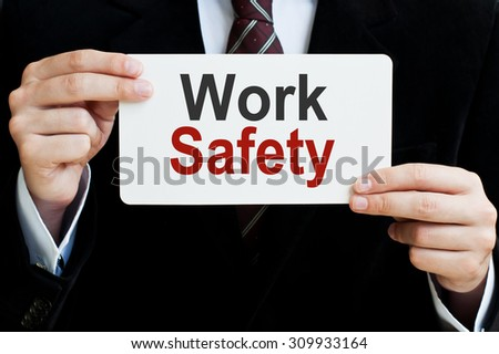 Work Safety. Man holding a card with a message text written on it - stock photo