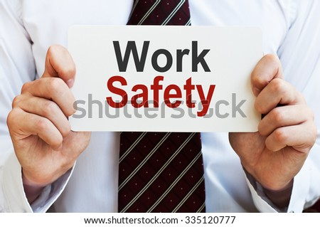 Work Safety. Man holding a card with a message text written on it.