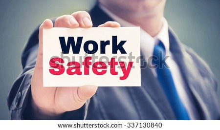 Work Safety word on the card held by a man hand, vintage tone - stock photo