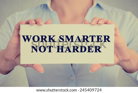 Work Smarter Not Harder Concept. Closeup retro style image business woman hands holding card with motivational message phrase text written on it isolated grey office wall background  - stock photo