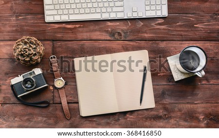 Work space on wood table of a creative designer or photographer with laptop, sketchbook, coffee and other objects of inspiration. Stylish home studio concept of technology trends. Vintage filter look - stock photo