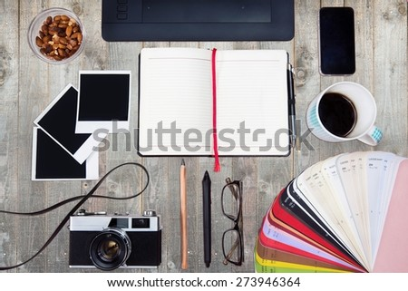 Work space on wood table with sketchbook, copy space, pencil, telephone. Creative concept of a designer's work office desk. Top view. - stock photo