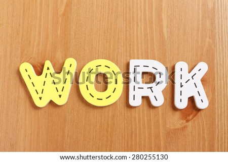 WORK, spell by woody puzzle letters with woody background