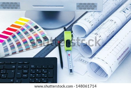 work table with drawings, a screen, a keyboard and measuring instruments - stock photo
