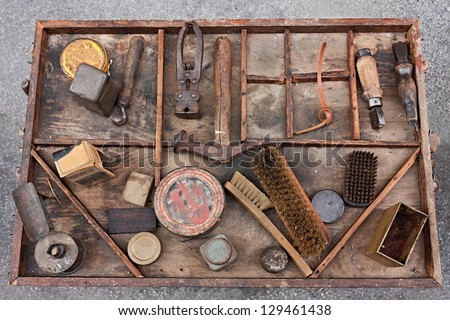 work table with old tools of the artisan shoemaker for repair, cleaning, polishing and finishing shoes - stock photo